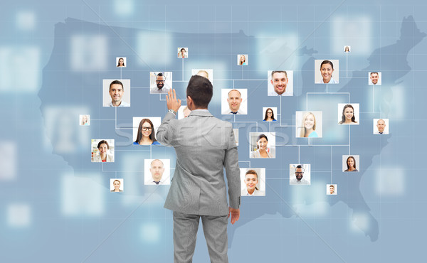 businessman touching virtual screen with contacts Stock photo © dolgachov