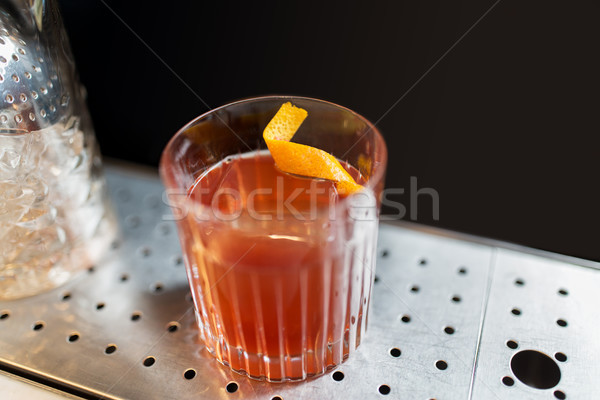 glass with cocktail and orange peel at bar counter Stock photo © dolgachov