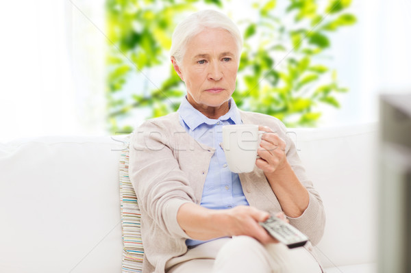 senior woman watching tv and drinking tea at home Stock photo © dolgachov