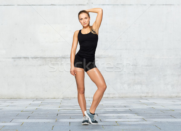 woman in sportswear posing over concrete wall Stock photo © dolgachov