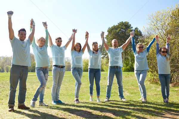 group of happy volunteers holding hands outdoors Stock photo © dolgachov