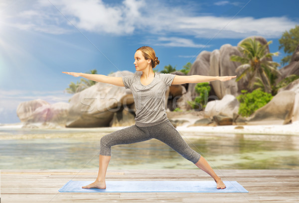 woman doing yoga warrior pose on beach Stock photo © dolgachov