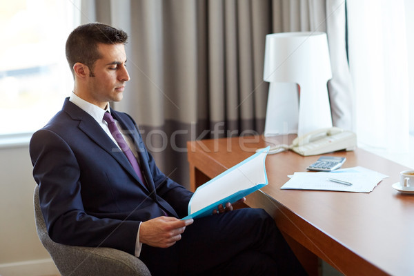 businessman with papers working at hotel room Stock photo © dolgachov