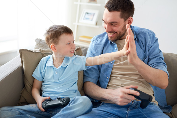 father and son with gamepads doing high five Stock photo © dolgachov
