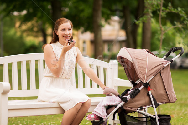 happy mother with smartphone and stroller at park Stock photo © dolgachov