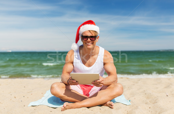 happy man with tablet pc on beach at christmas Stock photo © dolgachov