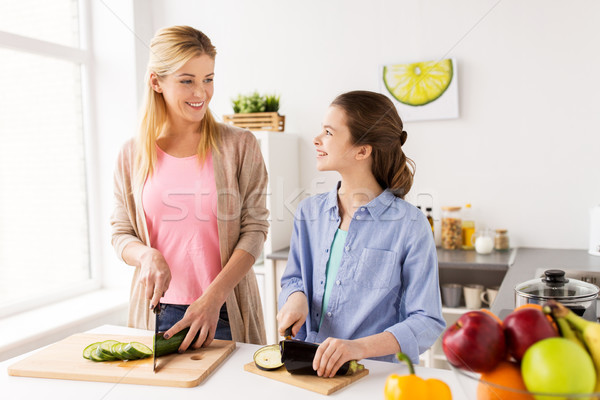 happy family cooking vegetables at home kitchen Stock photo © dolgachov