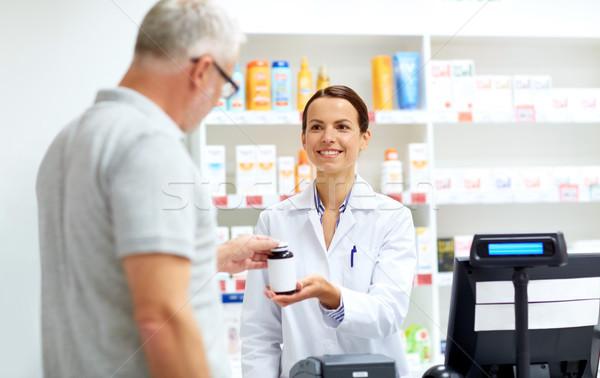 apothecary and senior customer at pharmacy Stock photo © dolgachov