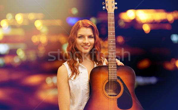 female musician with guitar over night city lights Stock photo © dolgachov