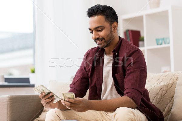 Stock photo: smiling man counting money at home
