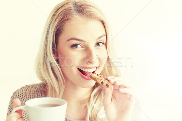 happy woman with tea eating cookie at home Stock photo © dolgachov