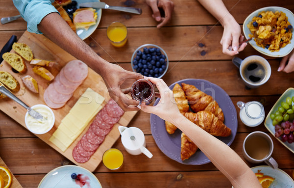 people having breakfast at table with food Stock photo © dolgachov
