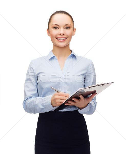 Jóvenes sonriendo mujer de negocios portapapeles pluma negocios Foto stock © dolgachov