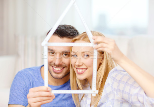 smiling couple with house from measuring tape Stock photo © dolgachov