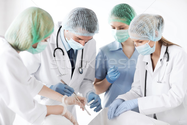 young group of doctors doing operation Stock photo © dolgachov