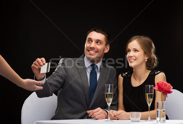 smiling couple paying for dinner with credit card Stock photo © dolgachov
