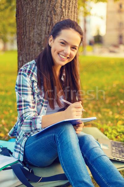 smiling teenager writing in notebook Stock photo © dolgachov