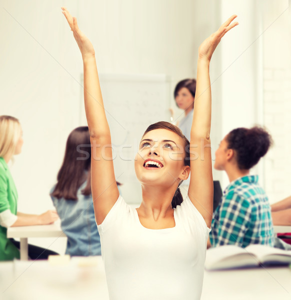 happy student girl with hands up Stock photo © dolgachov