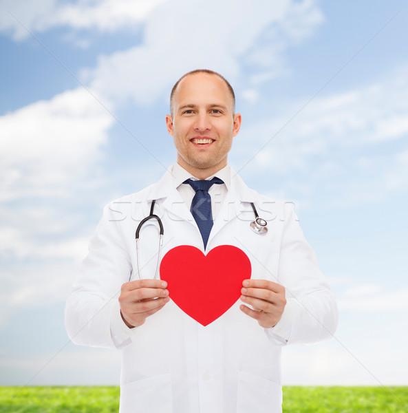 smiling male doctor with red heart and stethoscope Stock photo © dolgachov