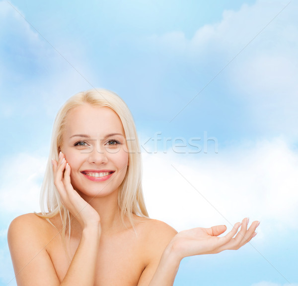 smiling woman holding imaginary lotion jar Stock photo © dolgachov