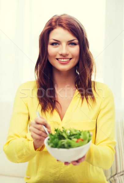 smiling young woman with green salad at home Stock photo © dolgachov