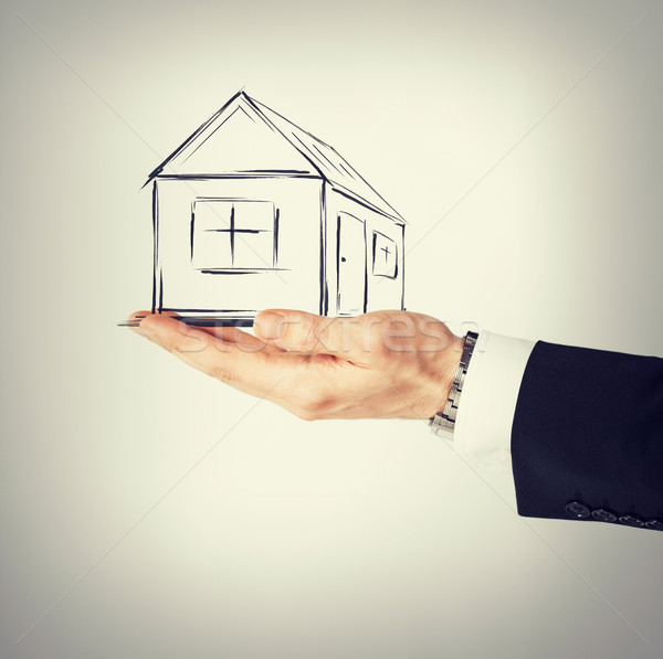 house on virtual screen in man hand Stock photo © dolgachov