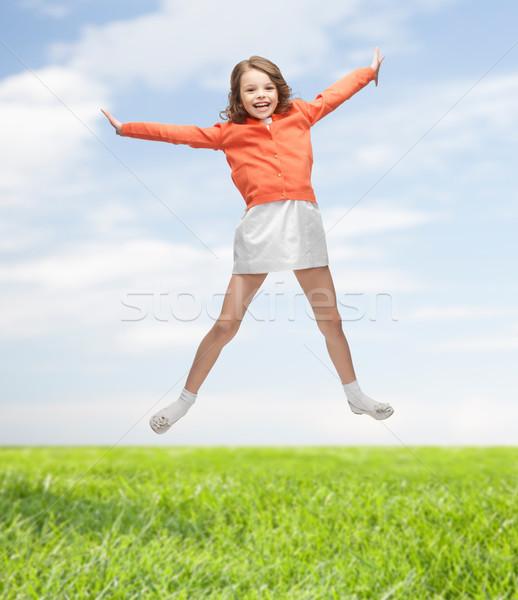 Happy girl przypadkowy ubrania skoki wysoki ludzi Zdjęcia stock © dolgachov