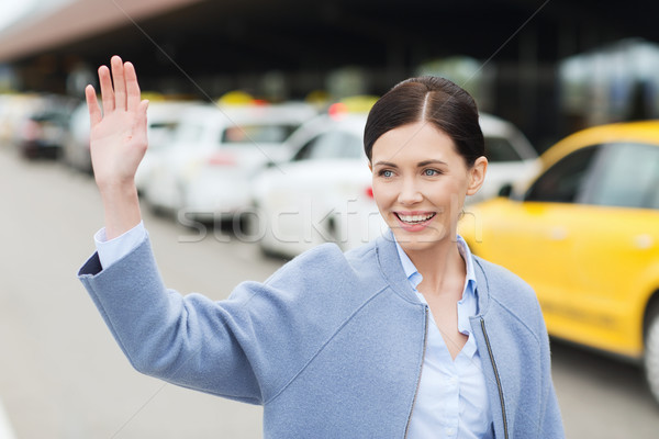 smiling young woman with waving hand over taxi Stock photo © dolgachov