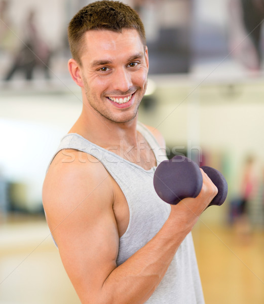 smiling man with dumbbell in gym Stock photo © dolgachov