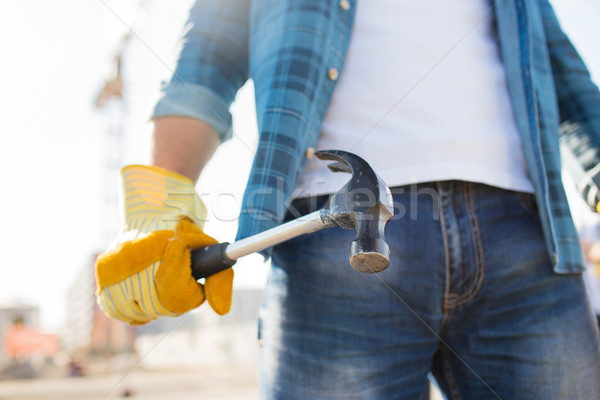 close up of builder hand in glove holding hammer Stock photo © dolgachov