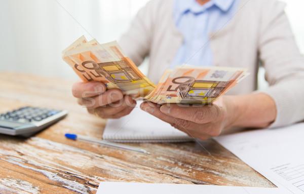 close up of senior woman counting money at home Stock photo © dolgachov