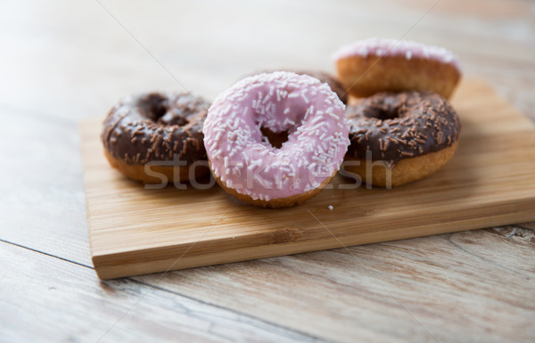 close up of glazed donuts pile on wooden table Stock photo © dolgachov