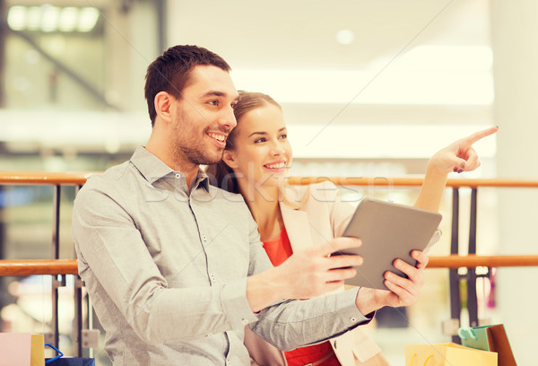 couple with tablet pc and shopping bags in mall Stock photo © dolgachov