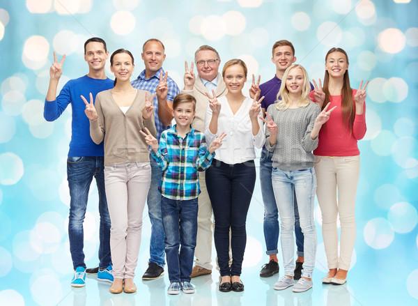 Csoport mosolyog emberek mutat béke kézjel Stock fotó © dolgachov