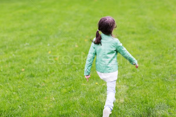 Stock photo: little girl walking along summer green meadow