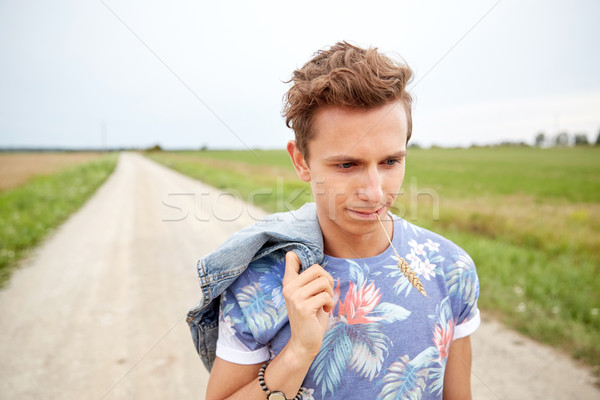 sad young hippie man walking along country road Stock photo © dolgachov