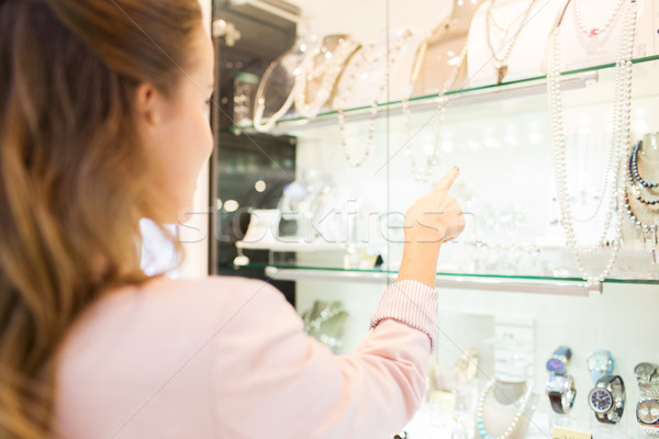 wooman pointing finger to window at jewelry store Stock photo © dolgachov