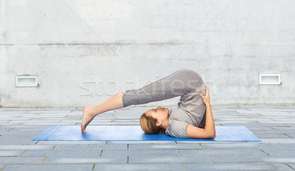 woman making yoga in plow pose on mat outdoors Stock photo © dolgachov
