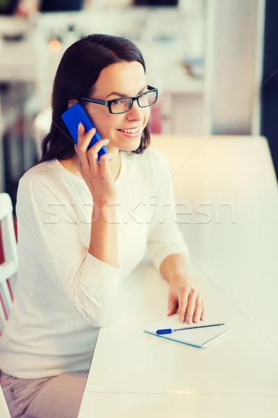 smiling woman calling on smartphone at cafe Stock photo © dolgachov