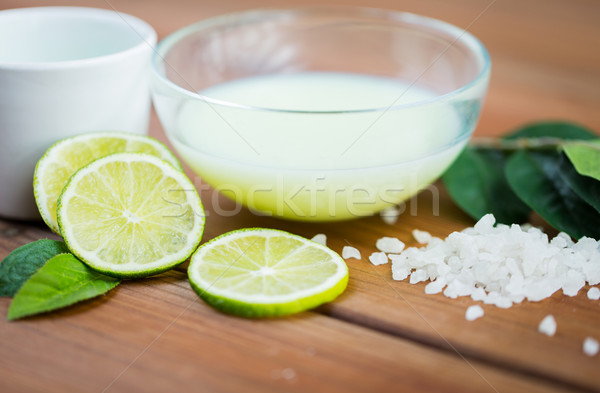 Stock photo: close up of body lotion in bowl and limes on wood
