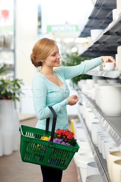 woman with basket choosing flower pot in shop Stock photo © dolgachov