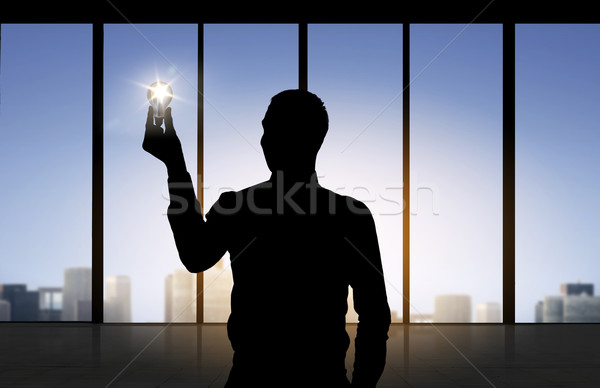 silhouette of businessman holding light bulb Stock photo © dolgachov