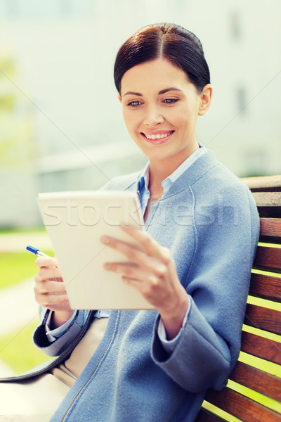 businesswoman reading notes in notepad outdoors Stock photo © dolgachov