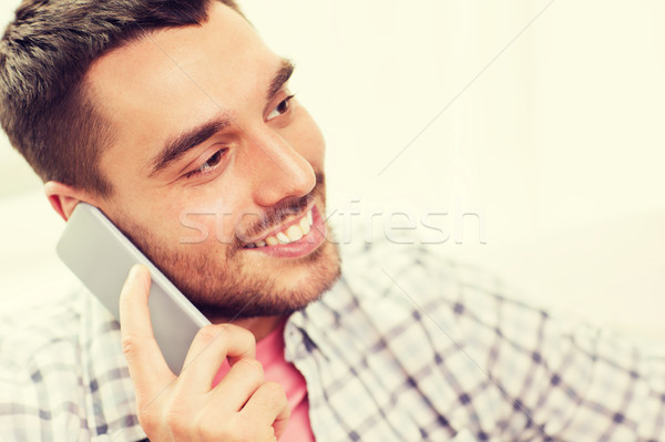 smiling young man calling on smartphone Stock photo © dolgachov