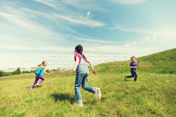 group of happy kids running outdoors Stock photo © dolgachov