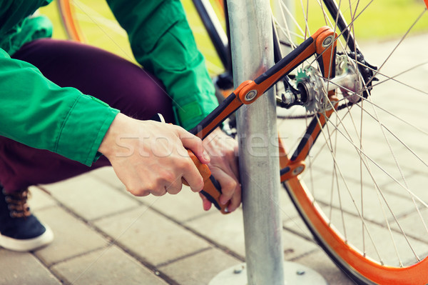 close up of man fastening bicycle lock on parking Stock photo © dolgachov