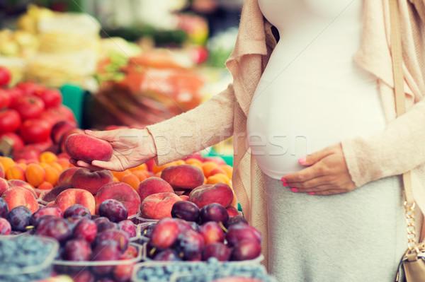pregnant woman choosing fruits at street market Stock photo © dolgachov