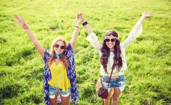 smiling young hippie women dancing on green field Stock photo © dolgachov