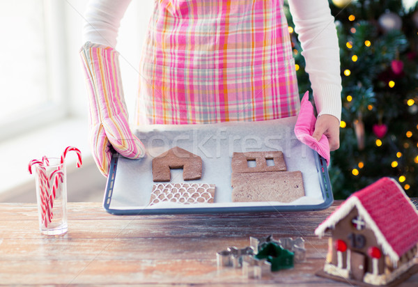 closeup of woman with gingerbread house on pan Stock photo © dolgachov