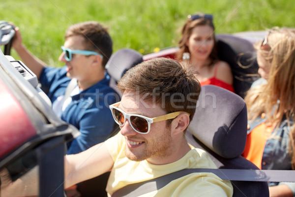 Szczęśliwy znajomych jazdy kabriolet samochodu odkryty Zdjęcia stock © dolgachov